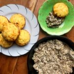 a plate of low carb Fathead biscuits, a pan of sausage gravy and a plate with a sausage gravy biscuit