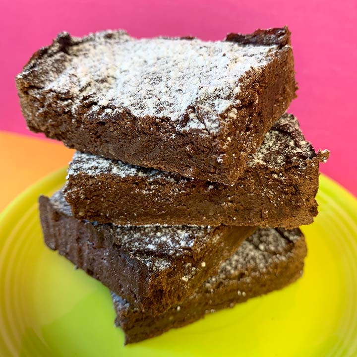 a stack of healthy avocado brownies on a green plate against a hot pink background