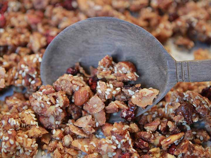 close up image of a wooden spoon digging into a pan of THM granola