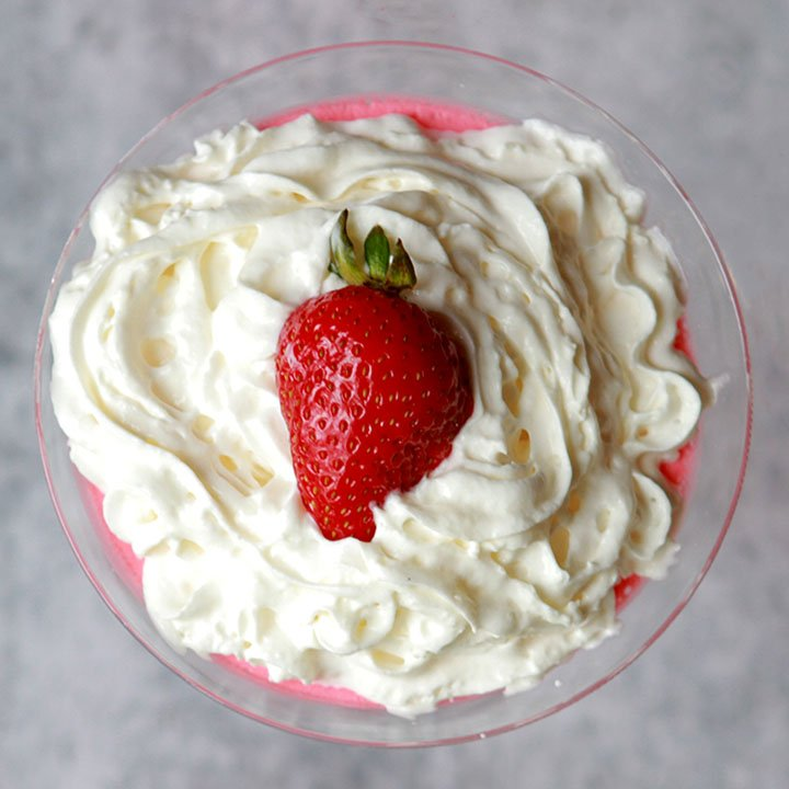a martini glass holds a portion of sugar free Jello gelatin with whipped cream and a strawberry on top