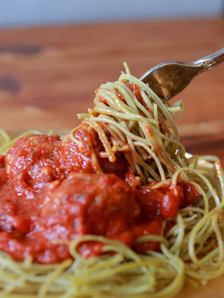 a fork twirls some edamame noodles and spaghetti sauce