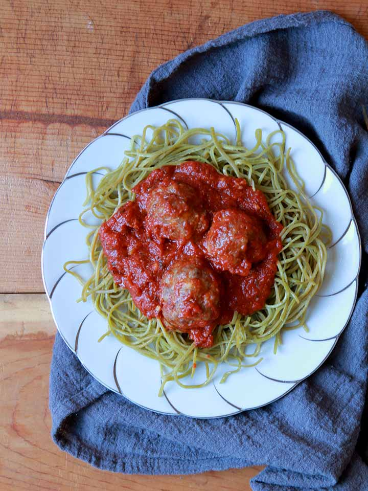 a plate of edamame spaghetti and meatballs on a fancy plate