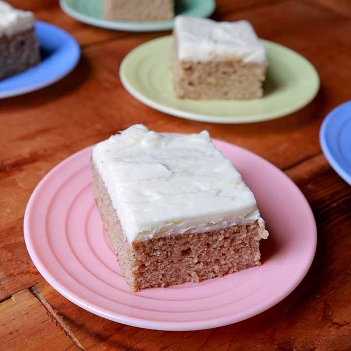 A piece of Keto spice cake on a pink plate with more pieces of cake in the background