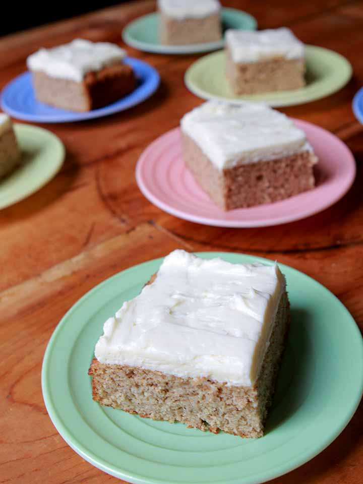 A piece of Keto spice cake on a green plate with more pieces of cake in the background
