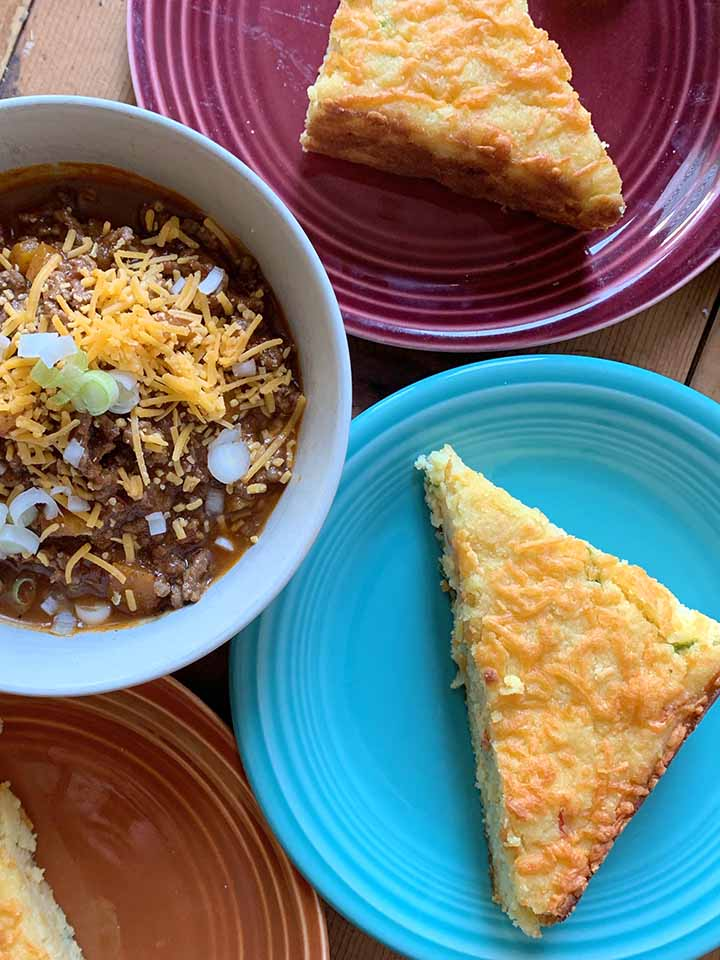 a bowl of low carb chili con carne next to 3 colored plates holding low carb cornbread