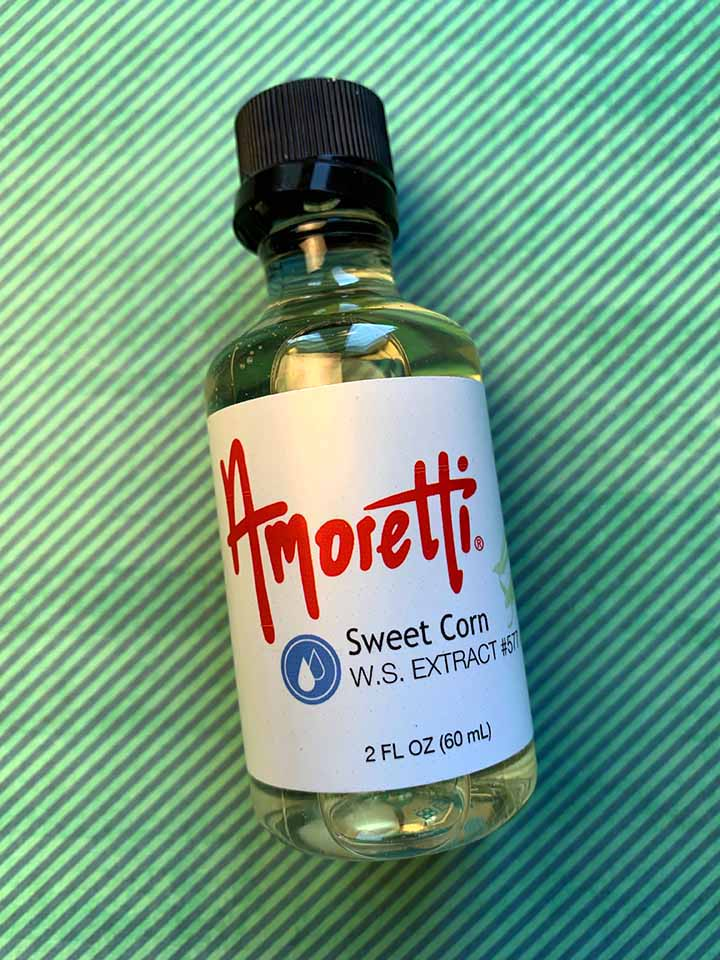 a bottle of Amoretti Sweet Corn Extract against a green striped background