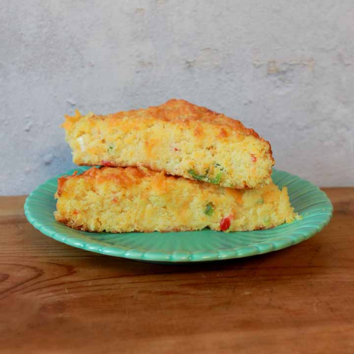 a stack of low carb Keto cheesy cornbread on a green plate on a wooden tabletop