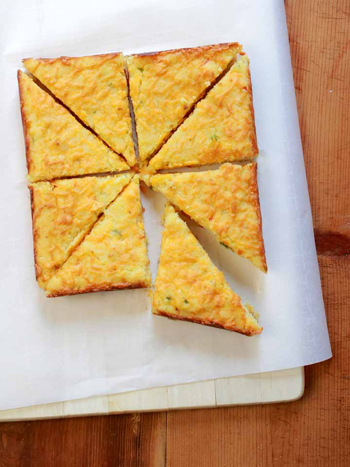 a top down view of 8 slices of low carb cheesy jalapeno cornbread against a white background