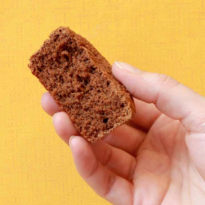 a hand holds a Keto chocolate muffin against a yellow background