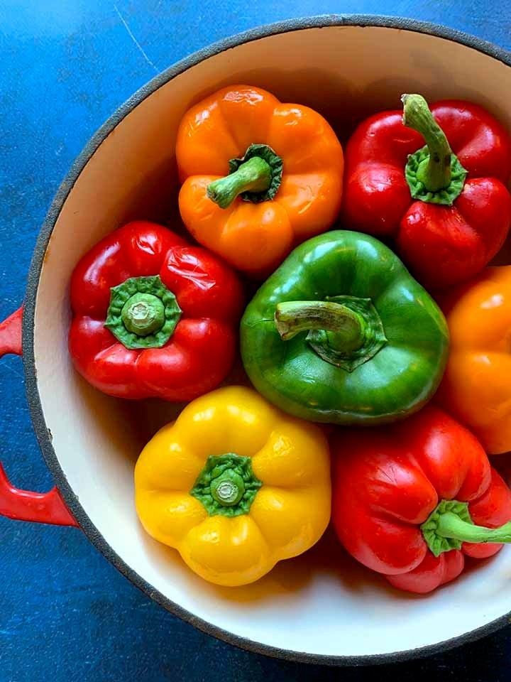 a dutch oven filled with fresh green, yellow, orange and red bell peppers