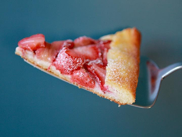 a slice of gluten free strawberry pastry against a blue background