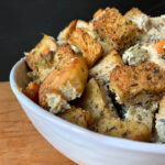 a side view of a white bowl holding Keto Thanksgiving Stuffing against a black background