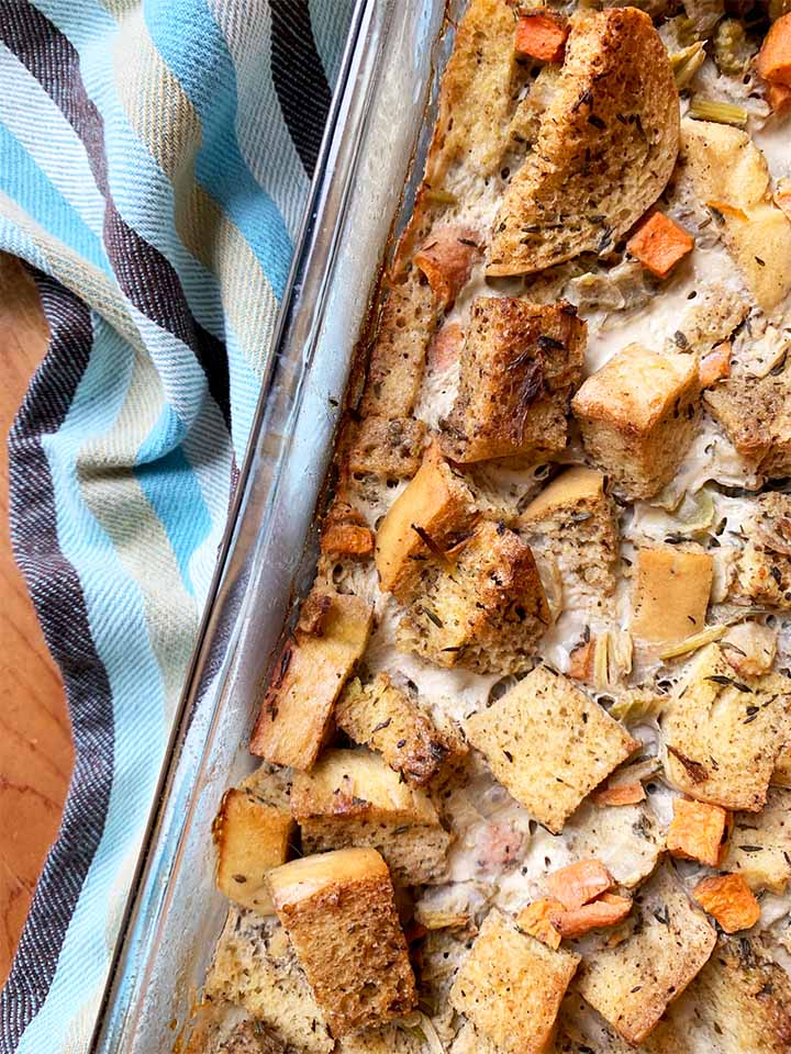 a casserole dish filled with Keto stuffing against a striped towel