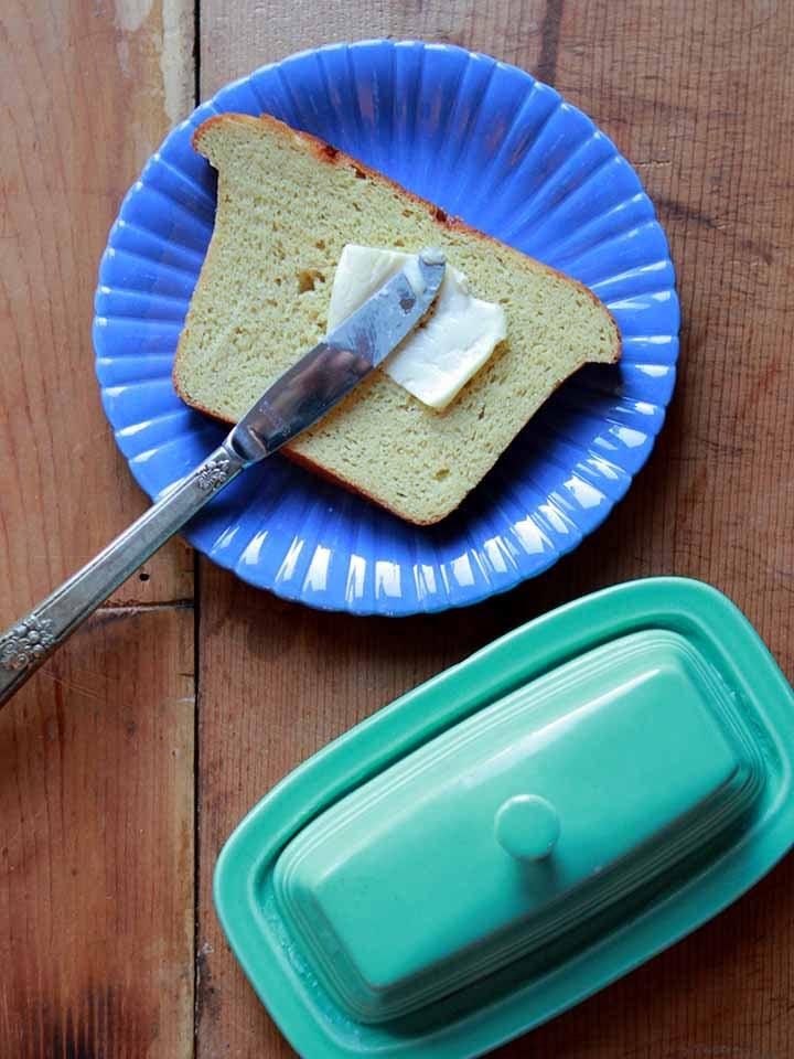 a knife spreads butter on a slice of Keto sandwich bread