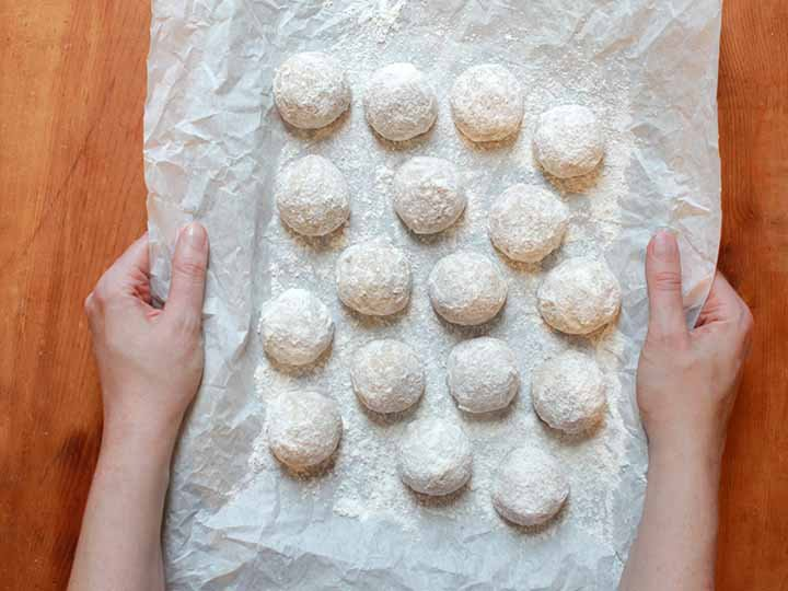 2 hands hold a tray of sugar-free Snowball Cookies