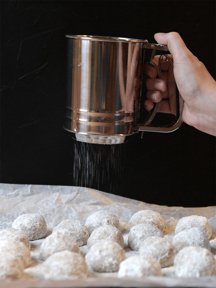 a hand sifted powdered sweetener onto gluten free Snowball Cookies