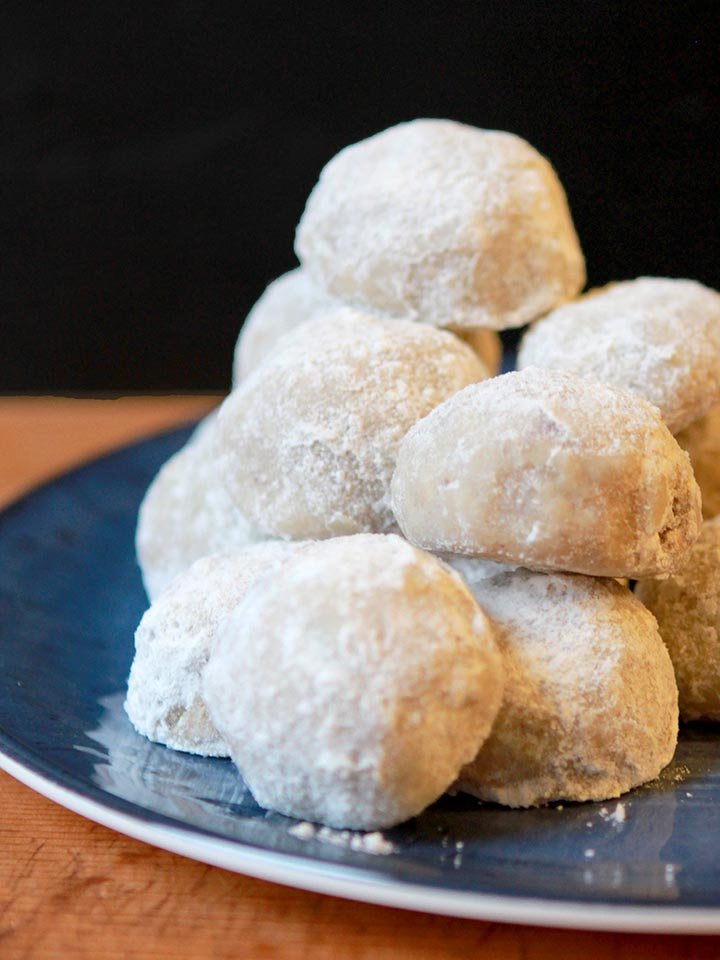 a stack of low carb Snowball Cookies against a black background