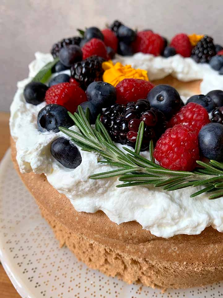 a low carb sponge cake with a wreath of berries and fresh herbs on top