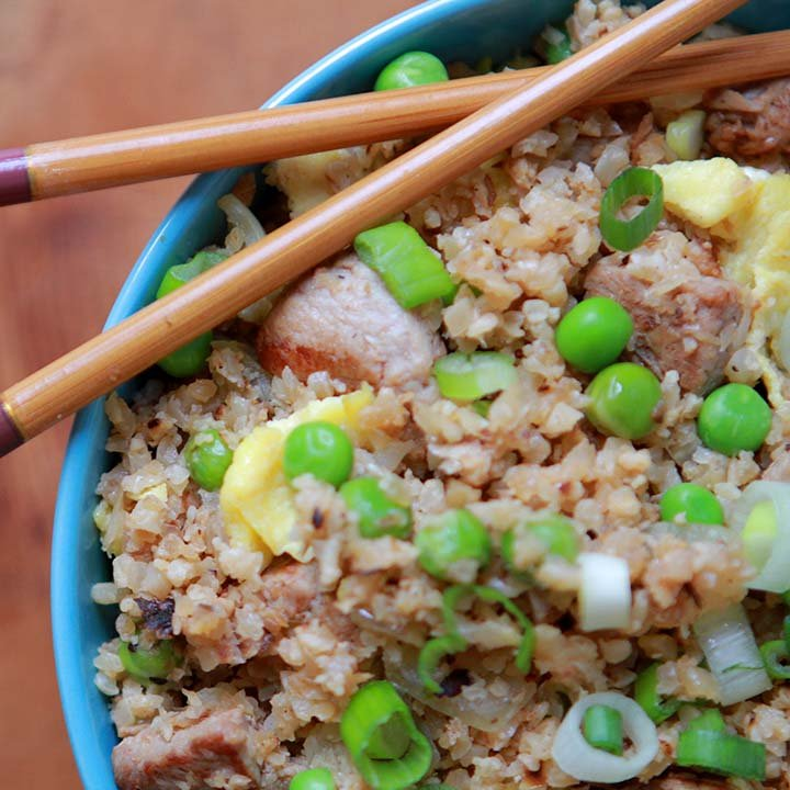 a top down close up of a bowl of healthy pork fried cauliflower rice