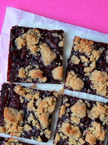 Keto blueberry breakfast bars against a hot pink background