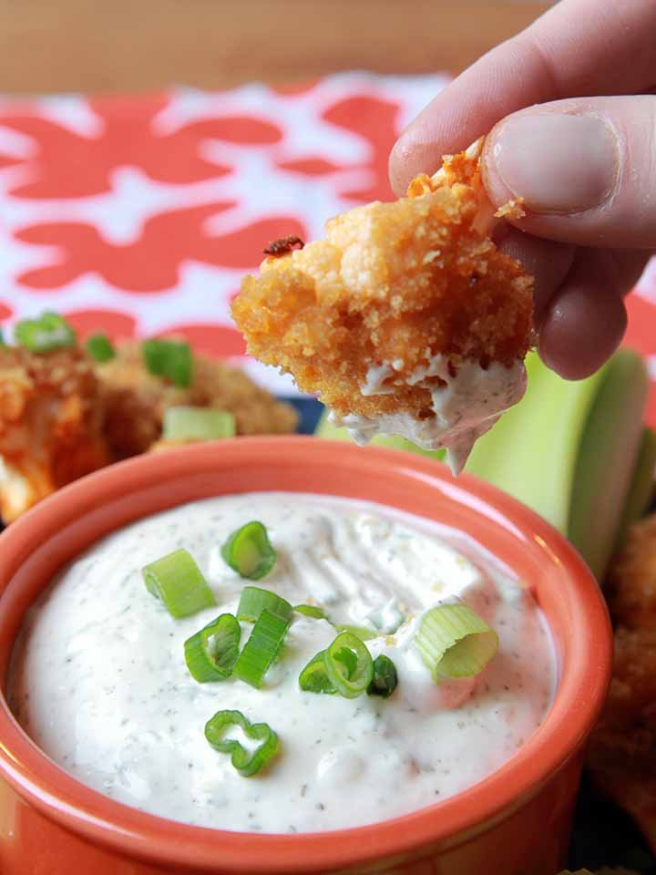 a hand is dipping a cauliflower floret into ranch dressing