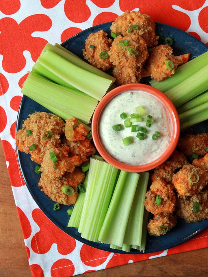 a top down view of a platter of low carb buffalo cauliflower with celery and ranch dressing