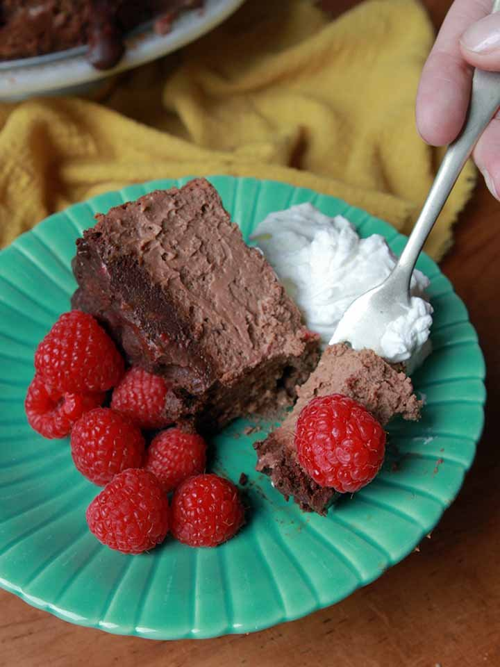 a hand takes a bite of healthy chocolate cheesecake