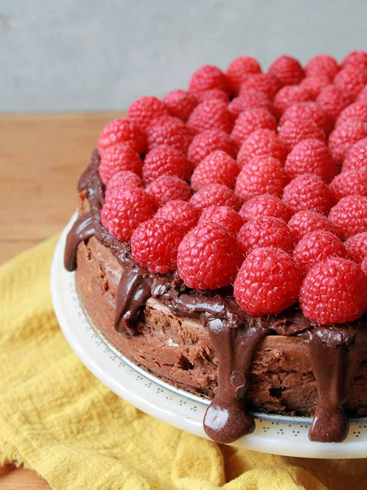 a side view of a Keto chocolate cheesecake with fresh raspberries on top