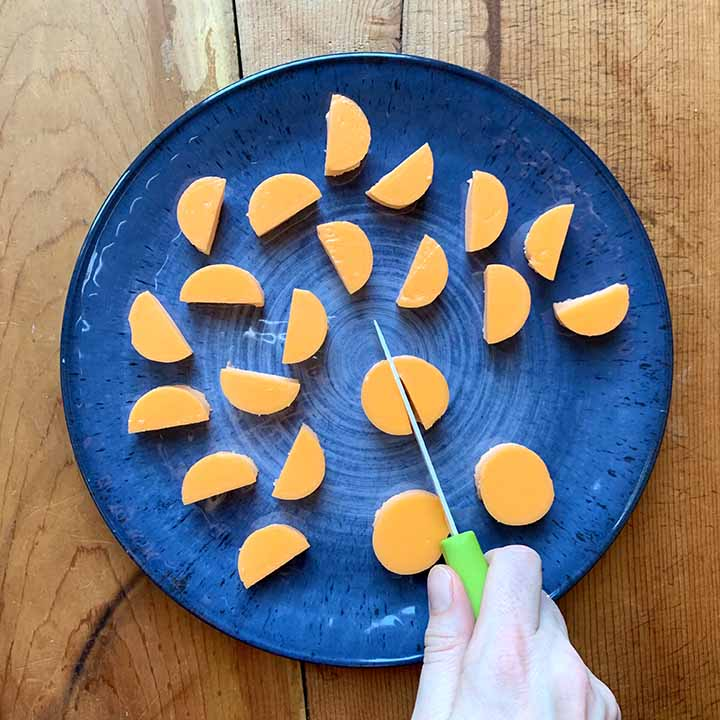 a hand cuts a circle of orange Jello in half with a knife