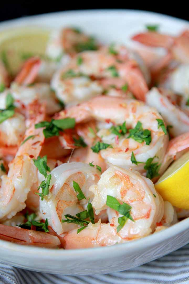 a white bowl filled with sauted shrimp in lemon butter sauce
