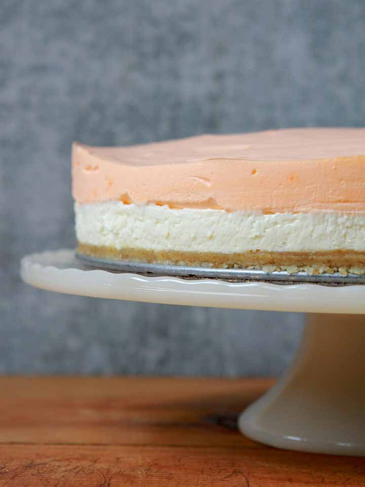 a Keto layered orange creamsicle cheesecake on a pedestal