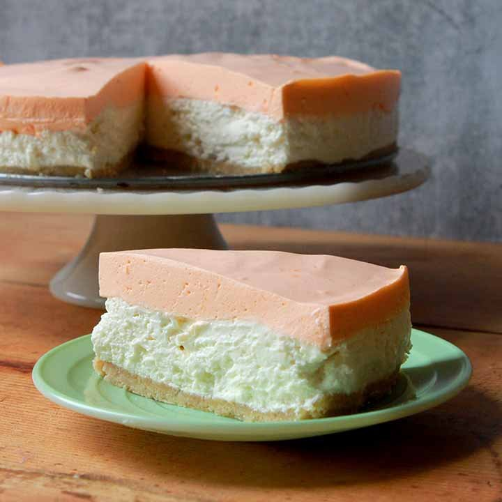 a slice cheesecake in front of the rest of the cheesecake on a pedestal