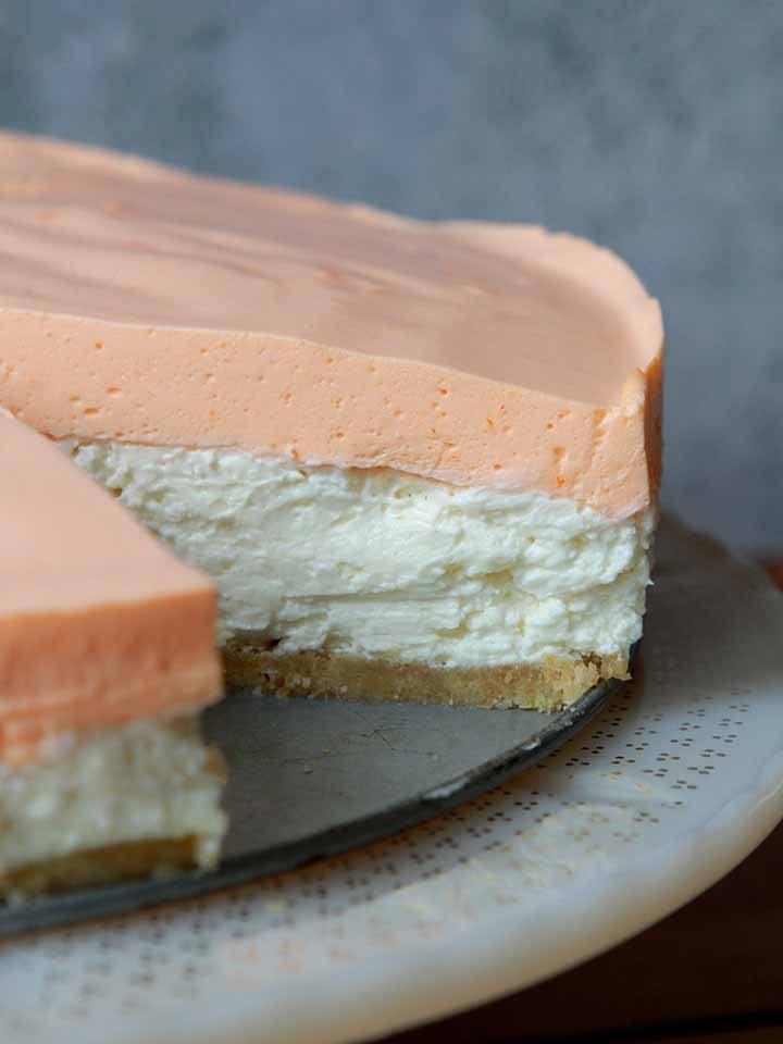 a side view of a Keto orange creamsicle cheesecake on a pedestal