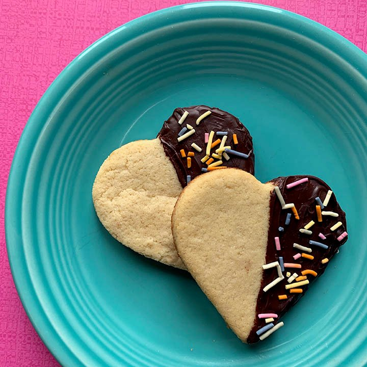 Two Keto heart shaped shortbread cookies on a blue plate