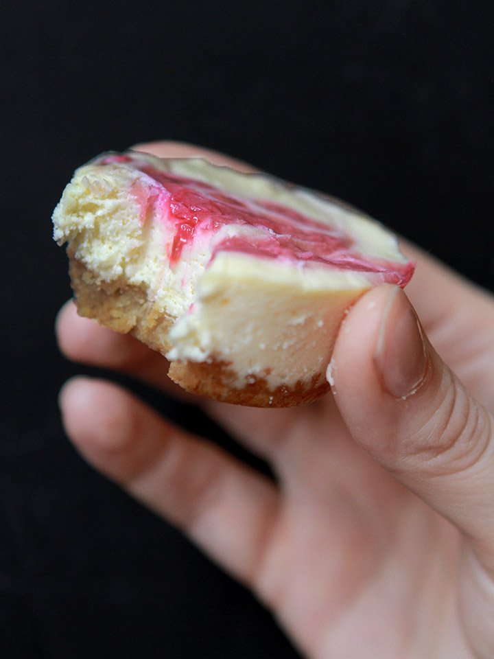 a hand holds a Keto mini cheesecake against a black background