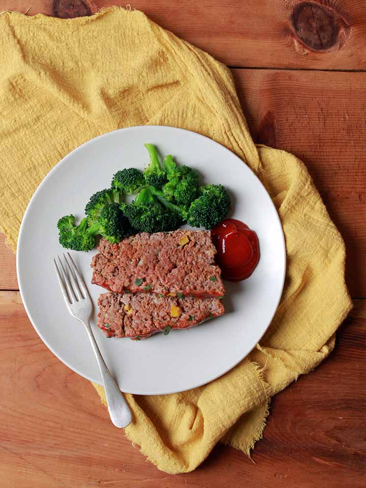 2 slices of Whole30 meatloaf on a plate with broccoli
