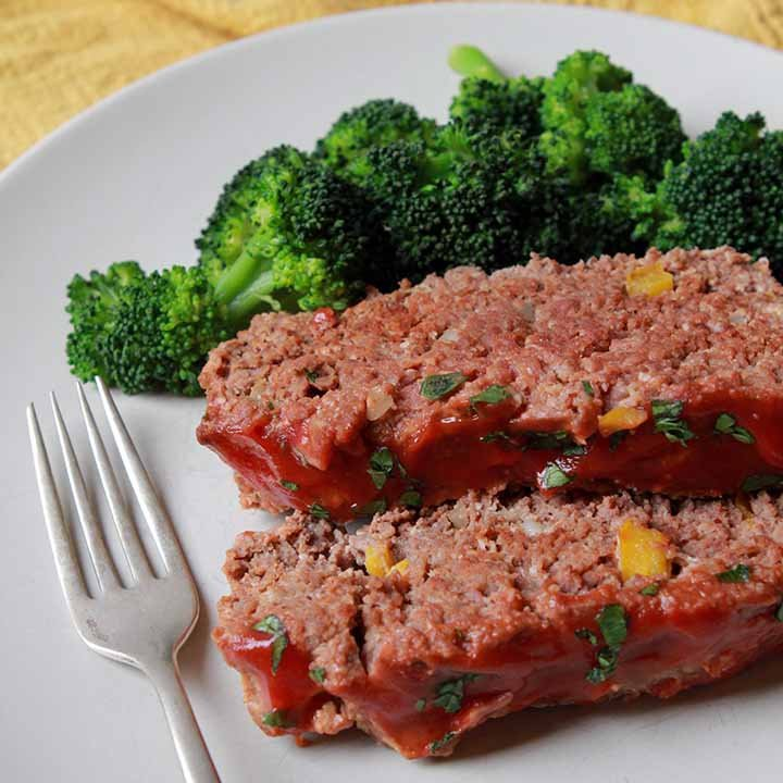 2 slices of Paleo meatloaf on a plate with broccoli