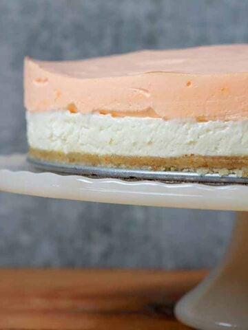 a Keto orange creamsicle layered cheesecake on a pedestal