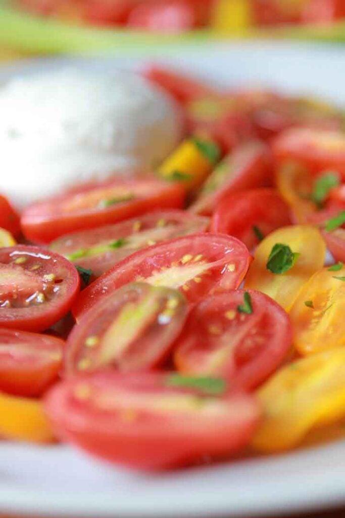 a close up of sliced grape tomatoes and buffalo mozzarella balls