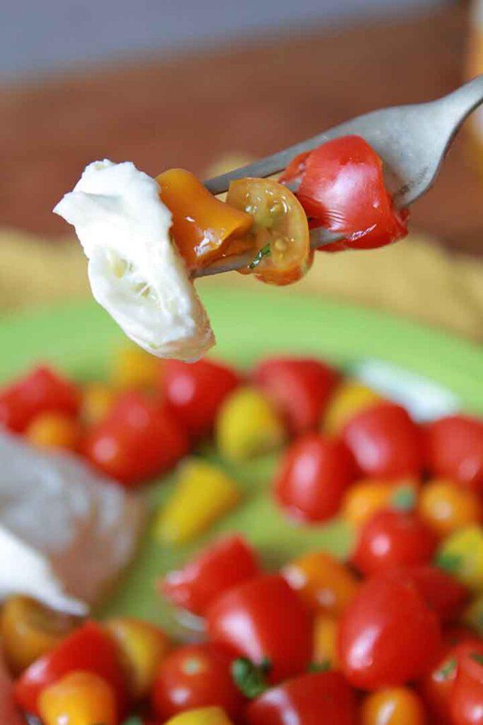 a fork holds a bite of keto mozzarella and tomato salad