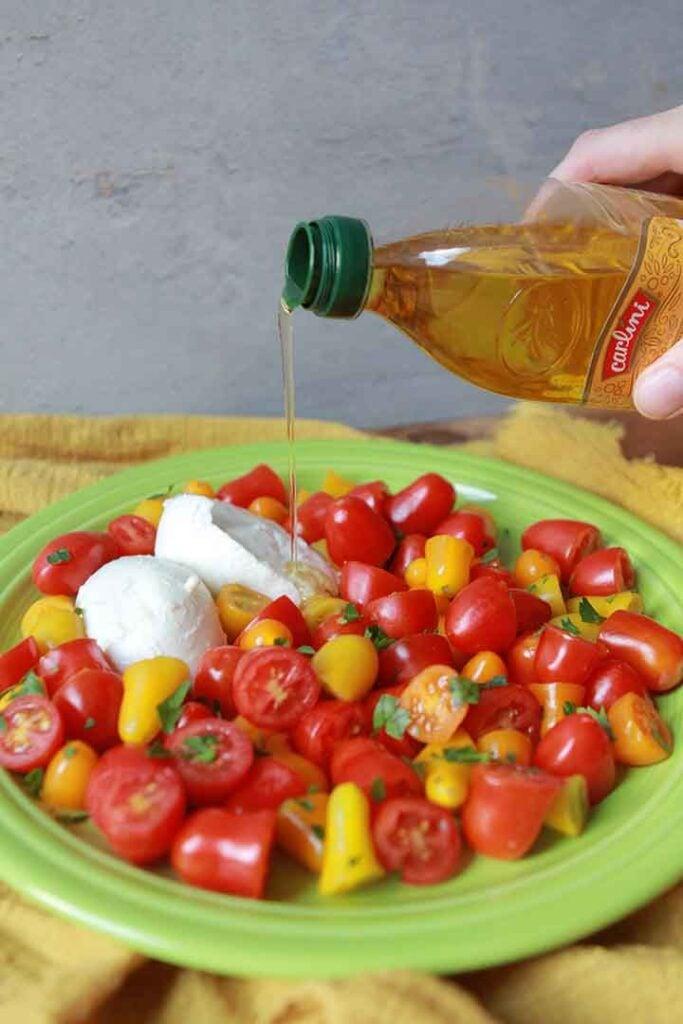 a hand pours olive oil onto a tomato and mozzarella salad