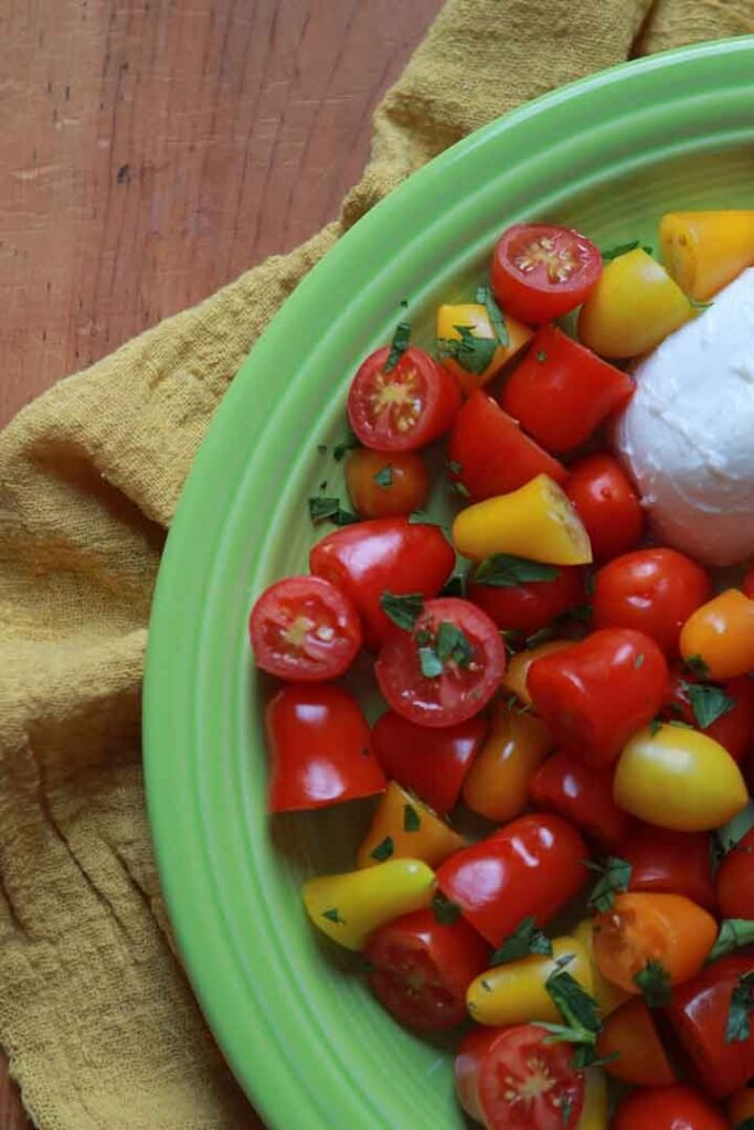 a green plate of cheese and tomato salad
