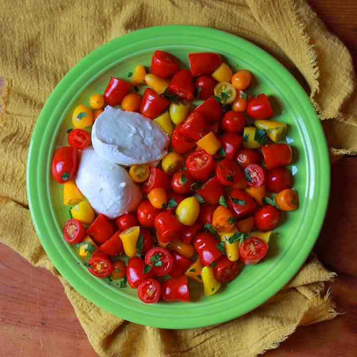 top down view of a green plate with an easy caprese salad