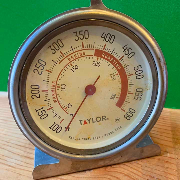 an oven thermometer against a green background