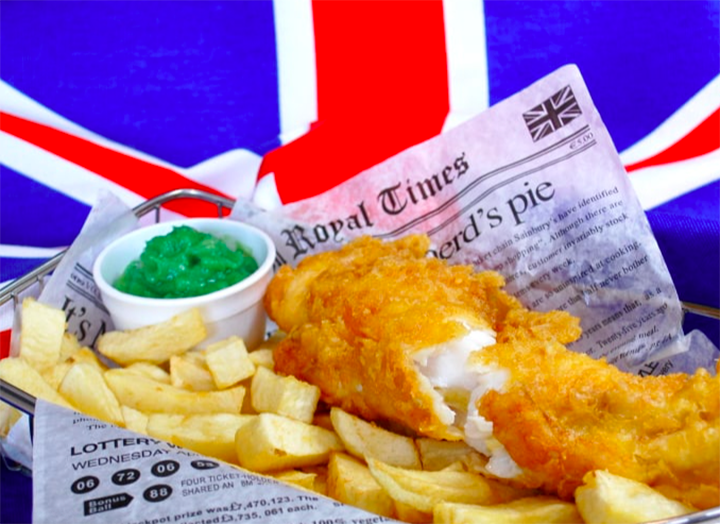 a basket of classic fish and chips in a newspaper with malt vinegar