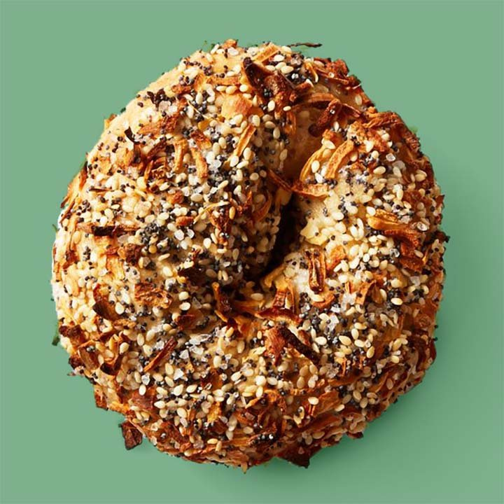 a classic everything bagel against a green background